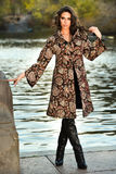 Attractive brunette model wearing elegant coat posing next to lake in the autumn park. Stock Photo
