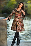 Attractive brunette model wearing elegant coat posing next to lake in the autumn park. Stock Image