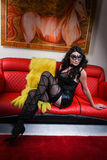 Attractive brunette model wearing sexy lingerie, mask and fur coat posing in luxury modern interior Royalty Free Stock Images