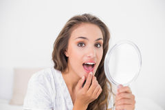 Attractive brunette opening mouth and holding mirror Royalty Free Stock Image