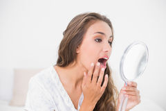 Attractive brunette opening mouth and looking at mirror Royalty Free Stock Photos