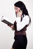 Attractive brunette with phone and datebook. Attractive young businesswoman calling by mobile and looking in datebook Stock Images