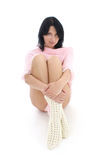 Attractive brunette in pink sweater sitting Stock Photo