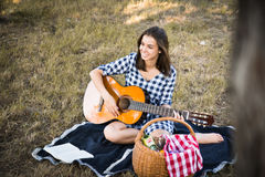 Attractive brunette playing guitar and smiling stock photos