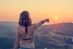 Attractive brunette pointing towards setting sun. Wearing swim suit Royalty Free Stock Photography