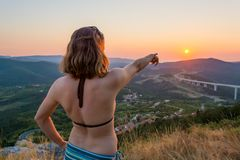 Attractive brunette pointing towards setting sun. Wearing swim suit Stock Photography