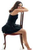 Attractive brunette posing on a chair Royalty Free Stock Photos