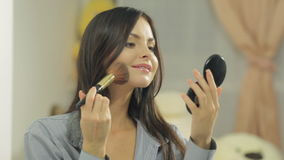 Attractive brunette powders her face with brush stock video footage