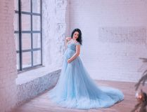 Attractive brunette pregnant girl in spacious room with white brick wall by window, posing in the photo, in blue long. Dress, embracing bulging tummy and gently stock images