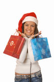 Attractive brunette is shopping with a Christmas hat Royalty Free Stock Images