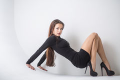 Attractive brunette in a short black dress, sitting on the floor stock photos
