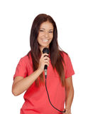 Attractive brunette singer dressed in red with a microphone Stock Photography