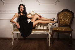Attractive brunette sitting on the couch Stock Images