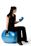 Attractive brunette sitting on fitness ball Stock Images