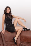 Attractive brunette sitting on sofa Royalty Free Stock Image