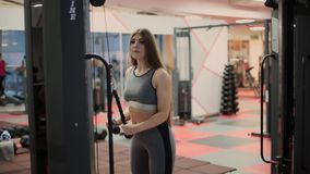 Attractive brunette with slender physique and cute face doing exercise on simulator. One person 20s 30s with sports. Clothing train in gym club indoors interior stock footage