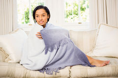Attractive brunette on the sofa under blanket Royalty Free Stock Photography