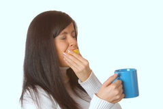 Attractive brunette squeezing lemon in a teacup Royalty Free Stock Image