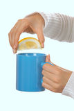 Attractive brunette squeezing lemon in a teacup Stock Photography