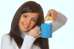 Attractive brunette squeezing lemon in a teacup Royalty Free Stock Photography