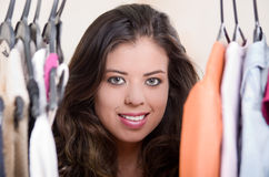 Attractive brunette standing with head in between clothes at clothing rack, shopping fashion concept Stock Images