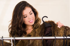 Attractive brunette standing looking through clothes on clothing rack, shopping fashion concept Royalty Free Stock Photos
