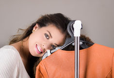 Attractive brunette standing smiling with head resting on clothing rack, shopping fashion concept Royalty Free Stock Photo