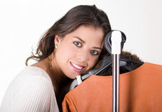 Attractive brunette standing smiling with head resting on clothing rack, shopping fashion concept Royalty Free Stock Photos