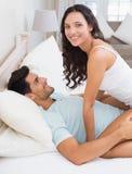 Attractive brunette straddling boyfriend on bed Stock Photos