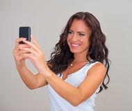 Attractive brunette taking selfie. Stock Photos