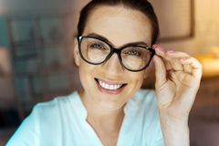 Attractive brunette touching her glasses. Give me your smile. Delighted woman expressing positivity and feeling happiness while looking at camera Royalty Free Stock Photos