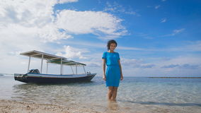 Attractive brunette in turquoise clothing is standing in the sea with traditional Balinese boat in the background. Fit stock video footage