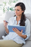 Attractive brunette using her credit card to buy online Royalty Free Stock Image