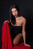Attractive brunette wear black dress kneeing on chair covered with red fabric Royalty Free Stock Photography