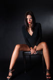 Attractive brunette wear black dress sitting on leather chair Royalty Free Stock Photography