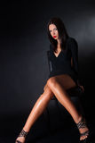 Attractive brunette wear black dress sitting on leather chair Royalty Free Stock Photos