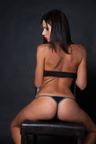 Attractive brunette wear underwear sitting on leather chair Royalty Free Stock Photos
