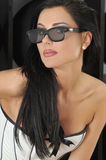 Attractive brunette wears 3D glasses and corset Stock Photo