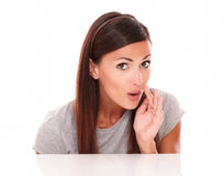 Attractive brunette whispering a secret to you royalty free stock image