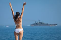 Attractive brunette in white swimwear observes ship waving his h Stock Photos