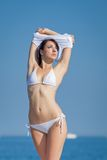 Attractive brunette in white swimwear undressing on the beach Stock Photos