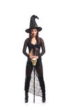 An attractive brunette witch in a huge dark hat Stock Photography