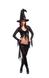 An attractive brunette witch in a huge dark hat Royalty Free Stock Photography