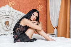 Attractive brunette woman on bed Royalty Free Stock Images