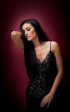 Attractive brunette woman in a black posing dramatic on purple background. Long hair female art portrait, studio shot Royalty Free Stock Photo