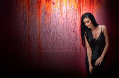 Attractive brunette woman in a black posing dramatic on purple background with red runoffs. Long hair female art portrait, studio Royalty Free Stock Images