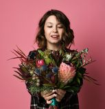 Attractive brunette woman in in a dark checkered dress holding bouquet of flowers in front of her. stock image