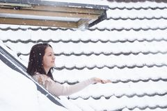 Woman reaching snowflakes through roof window. Attractive brunette woman dressed in a cozy sweater standing outside on her window reaching her hand to catch the stock photos