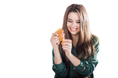 Attractive brunette woman eating a croissant on isolated background. Royalty Free Stock Image