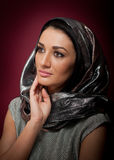 Attractive brunette woman in gray blouse and headscarf posing dramatic on purple background. Female art portrait, studio shot Royalty Free Stock Images